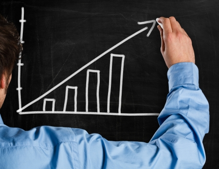 Man drawing a rising arrow on a blackboard photo