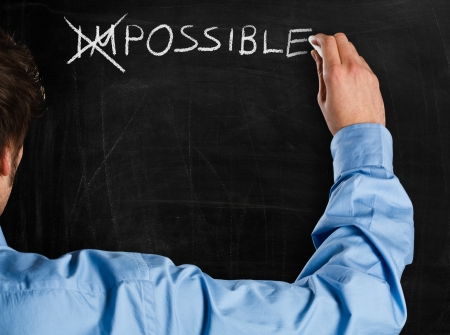 better: Man turning the word  Impossible  into  Possible