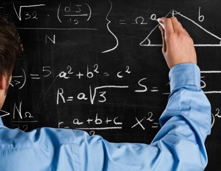 mathematics symbol: Man writing math formulas on a blackboard