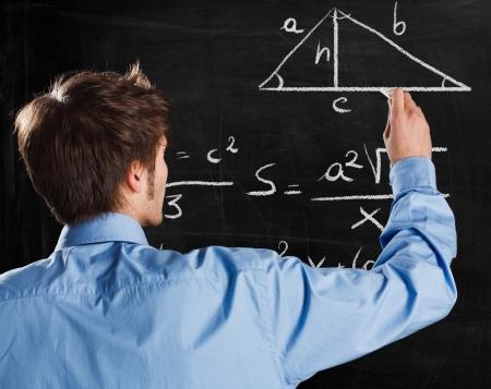 Man writing math formulas on a blackboard photo