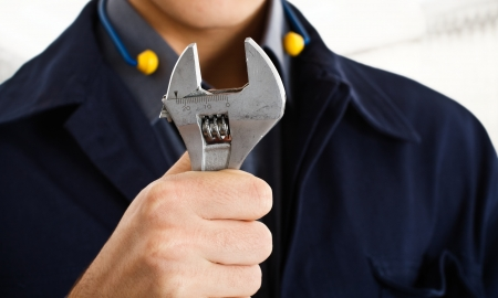 adjustable: Worker holding an adjustable wrench Stock Photo