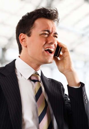Businessman screaming at the phone  Bright blurred background  photo
