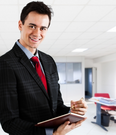 inspecting: Portrait of a young businessman writing something on a notebook in his office