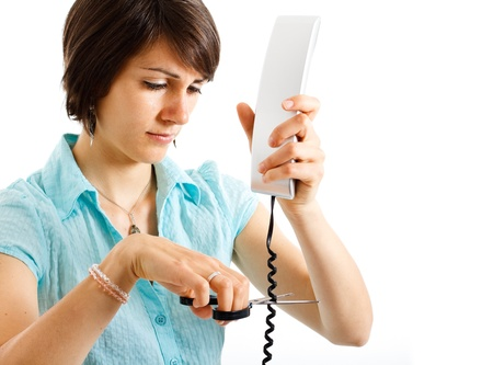 splitting up: Portrait of a stressed woman cutting a telephone cable