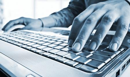 toetsenbord: Blauwe gestemde close-up van een werknemer met behulp van een laptop computer Stockfoto