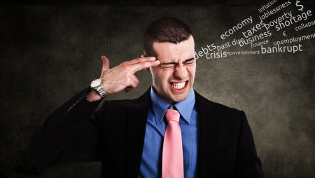 Conceptual image of a businessman shooting himself for business problems photo