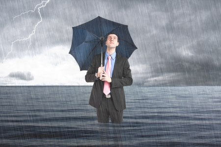 negativity: Businessman holding an umbrella in the sea Stock Photo