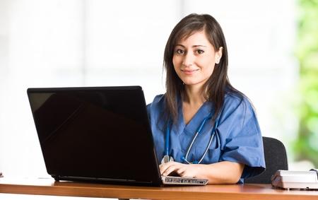 Portrait of a beautiful smiling nurse using a laptop photo