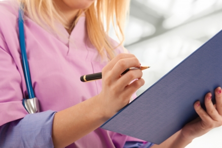 Young nurse writing medical records Stock Photo - 14598629