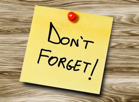 recordar: Nota de aviso amarillo en un fondo de madera