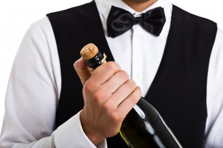 popping the cork: Portrait of a waiter holding a champagne bottle
