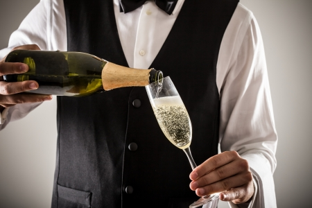 champagne bottle: Portrait of a waiter holding a champagne bottle