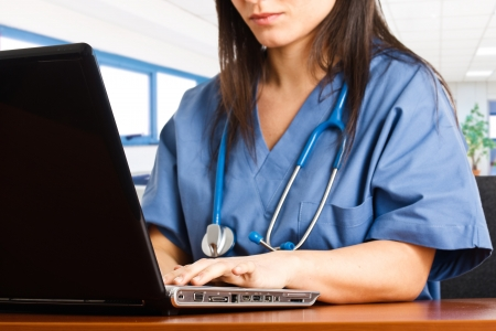 medico computer: Infermiera ricerca di qualcosa con il suo computer