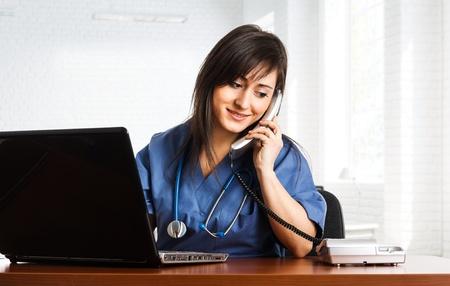 nurses: Portrait of a beautiful smiling nurse talking on the phone