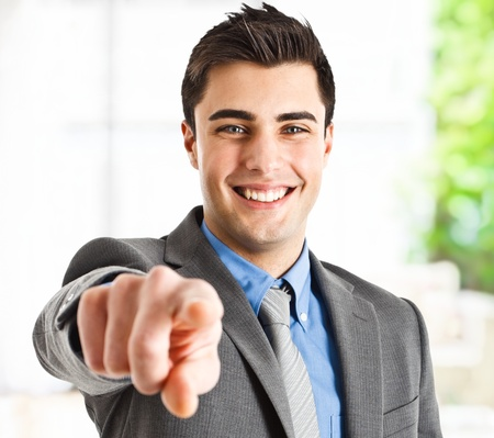 finger pointing: Handsome smiling businessman pointing his finger to you