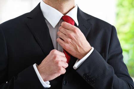 adjust: Businessman adjusting his necktie Stock Photo