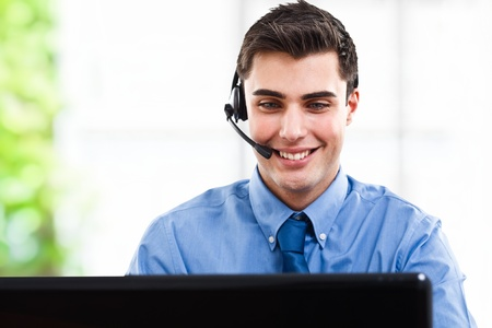 computer centre: Handsome man using an headset in front of a computer screen