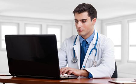 Doctor using a laptop computer on his desk photo