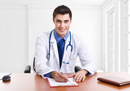 Doctor writing a prescription at his desk photo