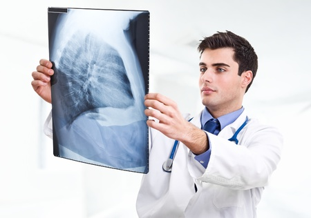 Handsome doctor examining a radiography Stock Photo - 14748199