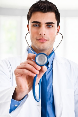 Handsome doctor holding a stethoscope photo
