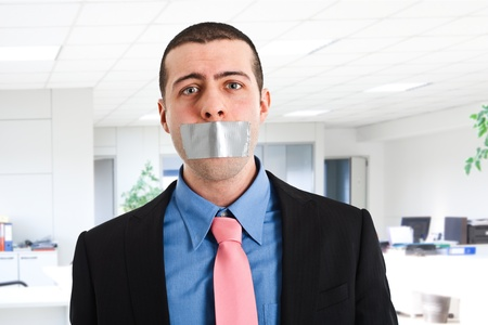 Portrait of a businessman having the mouth closed with tape Stock Photo - 14748487