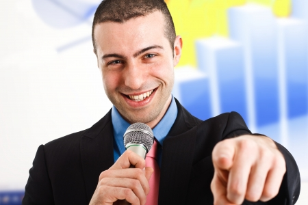Man holding a microphone while pointing his finger at you photo