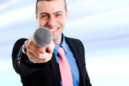 Handsome smiling man holding a microphone