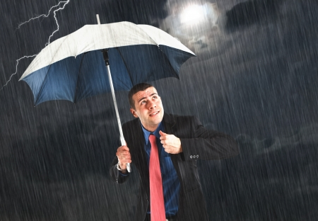 Businessman holding an umbrella in the storm photo