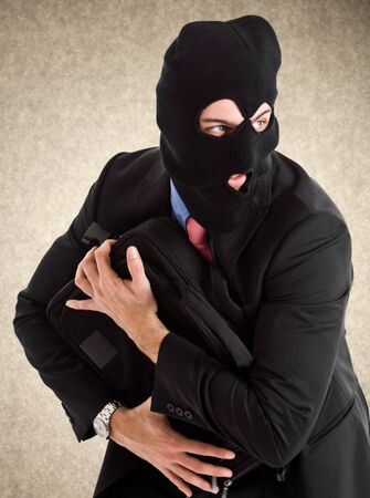 Portrait of a burglar running with a handbag photo