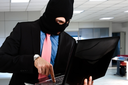 espionage: Hacker retrieving data from a laptop Stock Photo