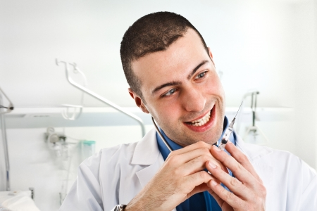 Crazy doctor looking at a syringe Stock Photo - 14748668