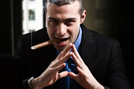 hombre fumando puro: Shady hombre fumando un cigarro en su oficina