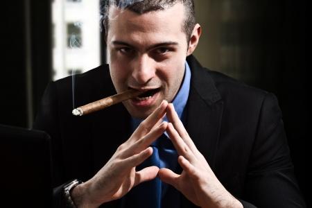 criminal activity: Shady man smoking a cigar in his office