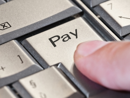 commerce communication: Close-up of a finger pressing the  pay  key Stock Photo