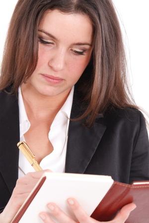 Young woman writing something using a golden pen photo