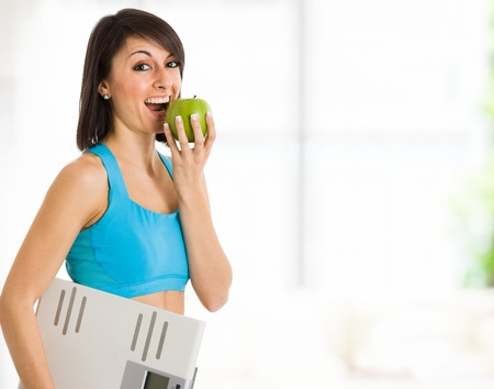 Beautiful woman eating a green apple photo