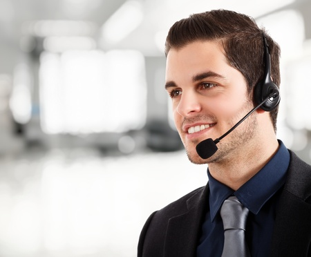 contact us: Portrait of a young happy phone operator  Bright blurred background