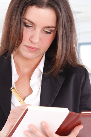 Young woman writing something using a golden pen photo