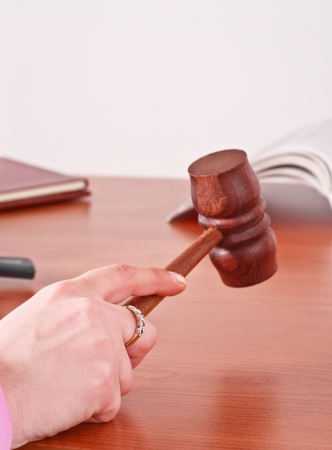 Judge handling a gavel in a courtroom photo