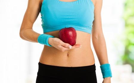 flat stomach: Donna che tiene una mela rossa