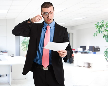 pricey: Businessman reading a document using a magnifying glass