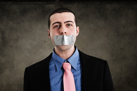repression: Portrait of a businessman having the mouth closed with tape