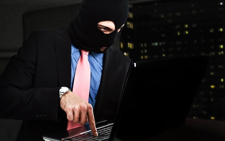 secret society: Thief hacking a computer Stock Photo