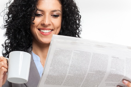 Beautiful woman reading a newspaper while drinking coffee photo
