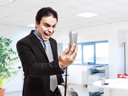 angry boss: Portrait of an angry businessman yelling at phone