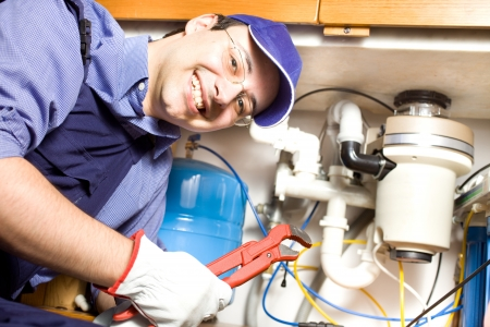 plumber: Portrait of a smiling plumber at work