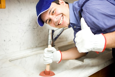 plumbing: Portrait of a smiling plumber using a plunger