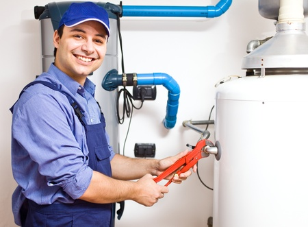 plumbing: Smiling technician repairing an hot-water heater Stock Photo