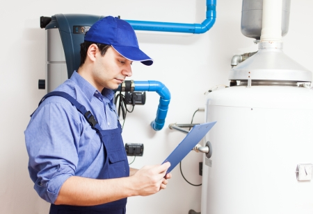 Technician servicing an hot-water heater Stock Photo - 15271579